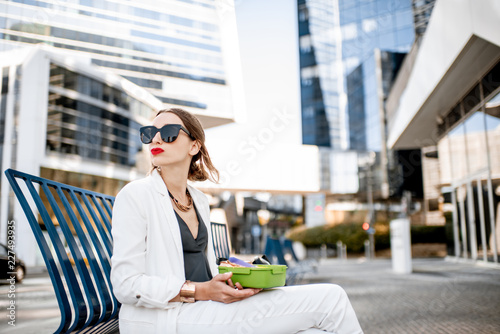 Photo Business woman having a snack with lunch box during a break sitting outdoors at