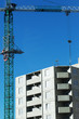 Construction of a residential high-rise building. Photo of a construction crane installing floor decks