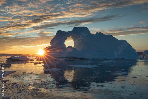 sunburst-za-masywna-gora-lodowa-z-dziura-w-polnocnym-sezonie-slonca-zatoka-disko-grenlandia