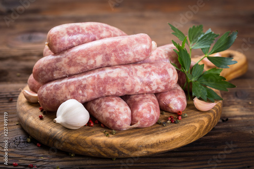 Raw sausages on the wooden board