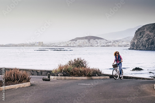 woman with long curly hair riding on bicycle looks around the natureand smiles. Free time concept in spring at the sea with ocean and cities in background. happy lifestyle for middle age people