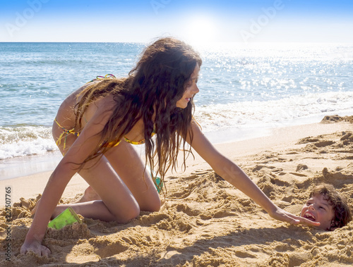Beach, joy and fun. Laughing, happy baby buried in the sand on a sandy tropical beach. Older sister sitting next