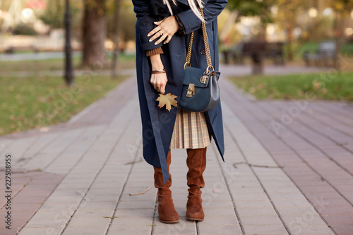 Fototapeta Beautiful fashionable woman walks through the autumn park in a blue coat with a bag in her hands. Details obraz