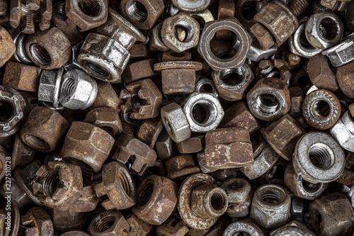 Fotografie, Obraz  Metal screw-nuts in set. Spent fasteners background.