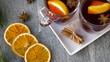christmas and seasonal drinks concept - glasses of hot mulled wine with orange slices and aromatic spices and fir branch on grey background