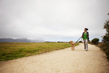 Woman Walking With Dog On Road By Grassy Field Against Cloudy Sky