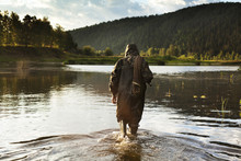 Man Carrying Fishing Net While Wading In Lake, Russia