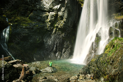 Distant view of hiker sitting on rock by waterfall at forest - 227512301