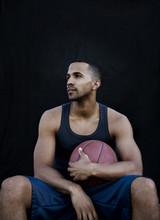 Man Holding Basketball Against Black Wall