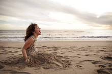 Girl Sitting With Legs Covered In Sand At Beach