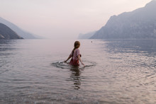 Woman In Water At Lake Garda Italy At Dusk