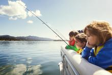 Three Children Fishing From Yacht