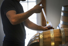 Midsection Of Man Collecting Whiskey From Barrel In Wineglass