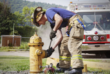 Firefighter Fixing Fire Hydrant In Field