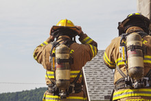 Rear View Of Two Firefighters