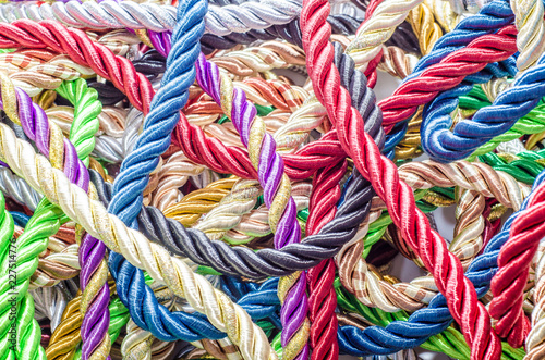 Fotobehang Paradijsvogel bloem Decorative multicolored cords of ropes scattered in a chaotic manner. Textile industry, thread, decoration