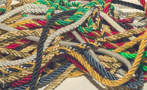 Multi-colored decorative rope scattered in a mess  Textile