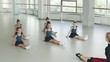 choreography lesson in the studio. children sit on the floor and repeat the movements of the teacher