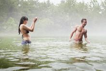 Woman Splashing Water On Man In Lake