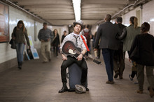Portrait Of Street Musician With Guitar In Subway