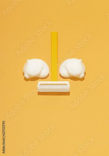 Overhead view of razor and shaving cream on orange background