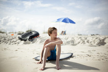 Boy Sitting On Surfboard On Be...