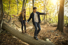Couple Balancing While Walking On Fallen Tree Trunk In Forest