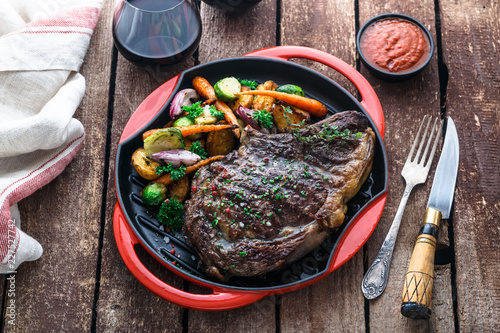 Cadres-photo bureau Steakhouse Juicy beef steak close view on iron cast pan with root vegetables