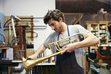 Man Shaping Trumpet In Workshop