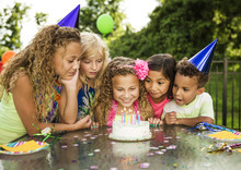 Children Looking At Birthday Cake On Table In Backyard