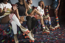 Friends Wearing Roller Skates Sitting On Multi Colored Sofa At Roller Rink