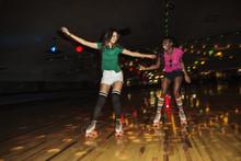 Friends Enjoying Roller Skating At Illuminated Roller Rink