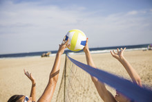 Friends Playing Beach Volleyball On Sunny Day