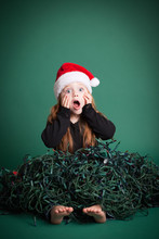 Stressed Christmas Girl In Tangled Lights, Isolated On Green