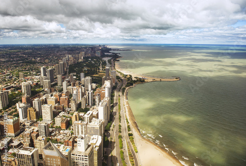 Aerial view of cityscape by sea against cloudy sky