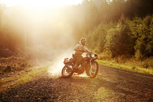 Man Riding Motorcycle On Gravel Road By Field