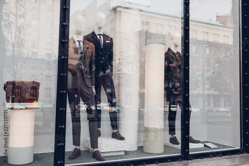 Fotomural Manikins dressed in autumn male outfits on showcase of a store in city center