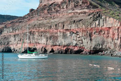 Poster Canarische Eilanden a boat moored under the large rocks of the Canary Islands, in Puerto Rico, Las Palmas de Gran Canaria