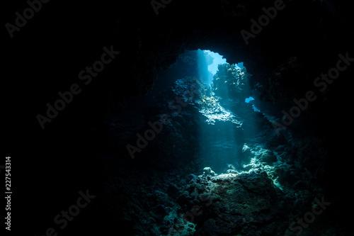 Fotobehang Koraalriffen Sunlight Descending Into Dark, Underwater Cavern