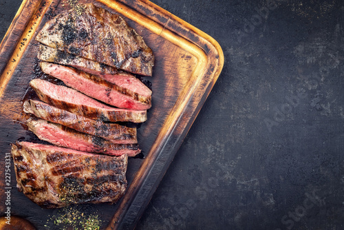 Fototapeta Barbecue dry aged wagyu flank steak sliced as top view on a burnt cutting board with copy space right obraz
