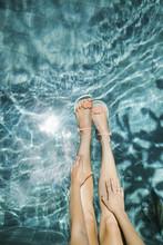 Female Legs Above Pool Water