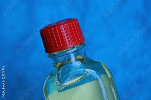 Fotografía  transparent plastic bottle with gun oil closed with a red cork