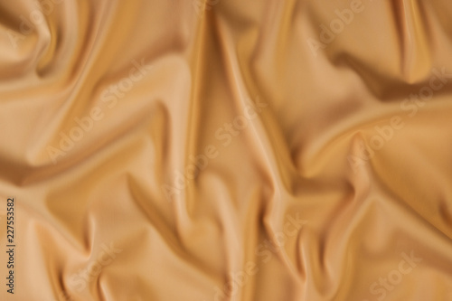 Fotografia  Beige silk fabric background, view from above