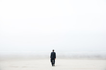 Businessman Walking On A Foggy Beach
