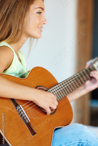 Smiling woman playing the guitar.