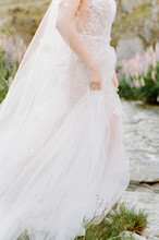 A Bride Delicately Holds Her Wedding Gown