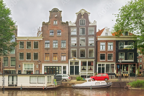 Old buildings near the one of the water canals in the historical part of Amsterdam, Netherlands.
