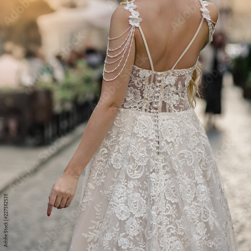 Foto  Bride in white silk dress with lace standing back on city street