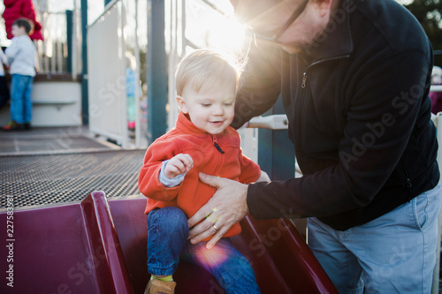 father helping a happy toddler on a slide