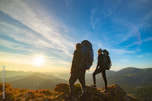 Fototapeta The couple standing on the mountain with a picturesque sunset background